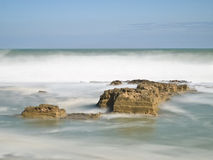 Rock in a Brave Sea. Rough stone rock in the middle of a raging sea, with the waves breaking on the coastline Royalty Free Stock Photos