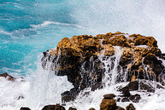 Rock in breaking wave. Rock being hit by a powerful wave of bright blue water Stock Image