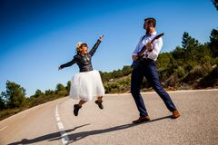 Rock bride with black leather jacket, boots and sunglasses poses with her boyfriend who plays an electric guitar in the middle of royalty free stock photo