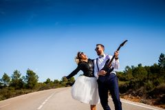 Rock bride with black leather jacket, boots and sunglasses poses with her boyfriend who plays an electric guitar in the middle of stock photo