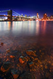 Rock and Brooklyn Bridge Stock Photography