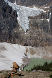 Rock cairn in front of angel glacier melting into  Stock Images