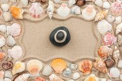 Rock cairn on the sand among sea shells Royalty Free Stock Photo