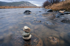 Rock cairn in shallow river. Royalty Free Stock Photo