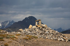 Rock cairn in sunlight on stormy day Stock Photo