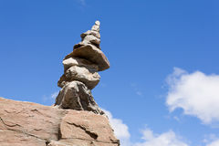 Rock cairn trail marker on boulder with blue sky Royalty Free Stock Photo