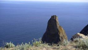 Rock and calm sea. Picturesque view to big coastal rock in calm blue sea in Crimea, cape Fiolent stock footage