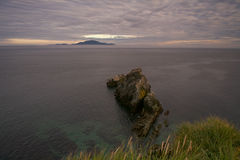 Rock at the Cape and the island in the sea on the horizon. Royalty Free Stock Image