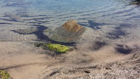 A rock on the center of a trasparent sea. In Baccu Mandara Stock Photography