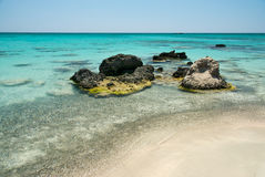 Rock in the clear blue water, Crete Royalty Free Stock Photo