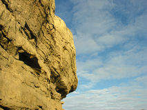 Rock cliff. A rock cliff against cloudy sky background Royalty Free Stock Photography
