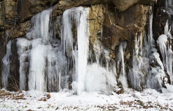 A rock cliff with frozen icles. Royalty Free Stock Images