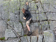 The rock-climber 01. The young man trying the forces in mountaneering stock image