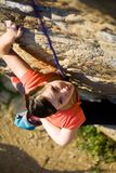 Rock-climber. The beautiful girl is engaged in rock-climbing on a vertical rock Stock Photo