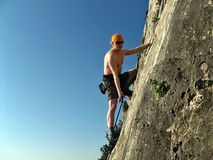Rock climber. Young naked male rock climber concentrating on lead climbing on rock against blue sky background Royalty Free Stock Image
