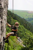 Rock climber. Young man in rappel after successfully climbing to the top Stock Images