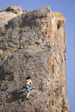 Rock Climber. Malibu, CA, USA - May 14, 2011:  An unidentified woman climbs up a sheer cliff on May 14, 2011 at Point Dume in Malibu, CA, USA.  The Point Dume Stock Images