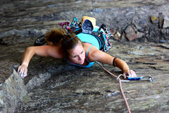 Rock climber. A female rock climber reaching for the summit Stock Photos