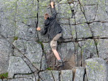 The rock-climber. The young man trying the forces in mountaneering stock photography