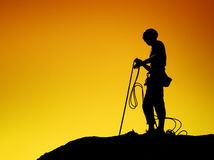 Rock Climber. Coiling rope silhouetted against the a sunset sky stock image