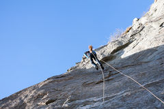 Rock climber abseiling off a climb Stock Photos