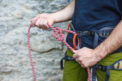 Rock climber adjusting harness by the rock face Royalty Free Stock Photo