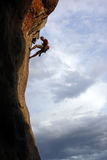 Rock climber against cloudy sky background Royalty Free Stock Photography