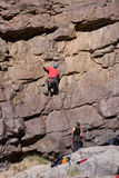 Rock climber with belaying Stock Images