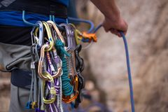 A rock climber belays his partner while he climbs up a rock wall stock image