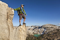 Rock climber celebrates on the summit. Royalty Free Stock Image