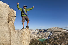 Rock climber celebrates on the summit. Royalty Free Stock Photos