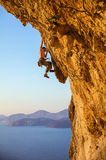 Rock climber on challenging route at sunset Stock Photography