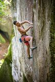 Rock climber on challenging route on vertical cliff Stock Image
