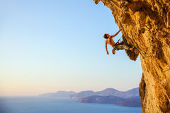 Rock climber on cliff at sunset. Young man looking up while climbing challenging route on cliff, view of coast below Royalty Free Stock Photography