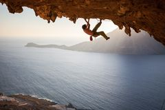 Rock climber climbing along roof in cave at sunset Stock Image