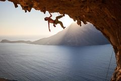 Rock climber climbing along roof in cave at sunset Stock Images