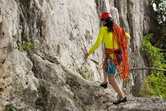 Rock climber standing in front of mountain cliff outdoor Stock Photos