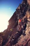 Rock climber climbing at seaside mountain cliff Stock Image