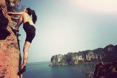 Rock climber climbing at seaside mountain rock Stock Images