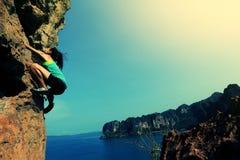 Rock climber climbing at seaside mountain rock Stock Image
