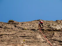 Rock climber climbing a sloping rock wall Royalty Free Stock Image