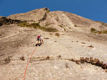 Rock climber climbing a sloping rock wall Stock Image