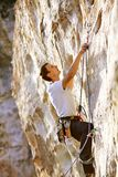 Rock climber climbing up a cliff Stock Photos