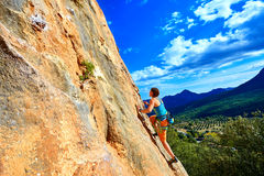 Rock climber climbing up a cliff Stock Photography