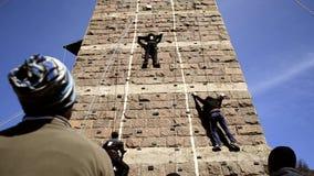Rock climber climbing up a cliff stock video footage