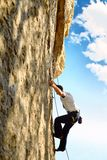 Rock climber climbing up a cliff Royalty Free Stock Photos