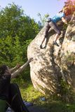 Athletes are bouldering outdoors. A rock climber climbs a rock and his partner insures. Athletes are bouldering outdoors. Group of friends involved in sports in Royalty Free Stock Photo