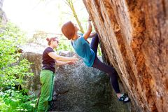 Athletes are bouldering outdoors. A rock climber climbs a rock and his partner insures. Athletes are bouldering outdoors. Group of friends involved in sports in Stock Photos