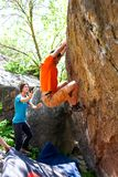 Athletes are bouldering outdoors. A rock climber climbs a rock and his partner insures. Athletes are bouldering outdoors. Group of friends involved in sports in Stock Image