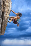 Rock climber clinging to a cliff. Stock Images